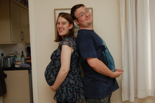 Photo of pregnant mum and dad, back to back, with dad's belly sticking out like mum's bump