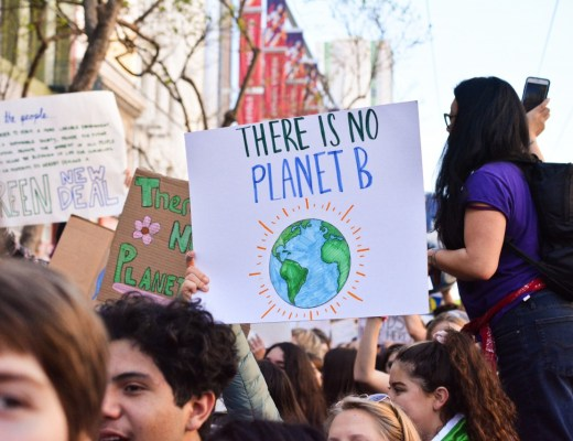 "climate change march with someone holding a sign saying ""There is no Planet B"" and a drawing of the earth"