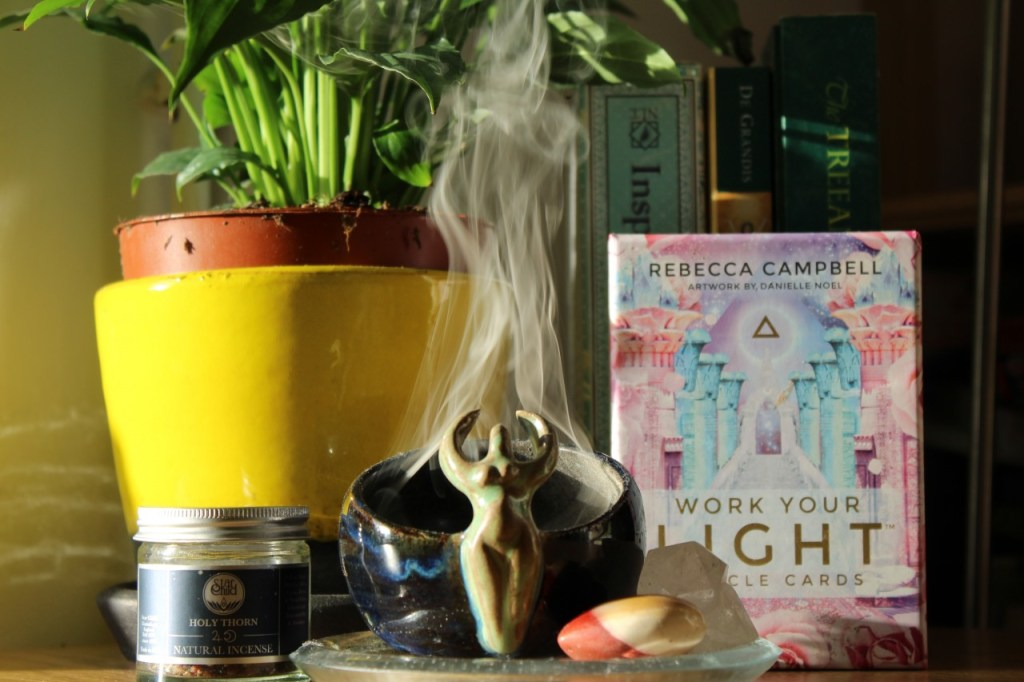 Image of a goddess incense bowl with smoke rising from it, with crystals beside it, and a yellow plant pot and oracle card deck behind it.