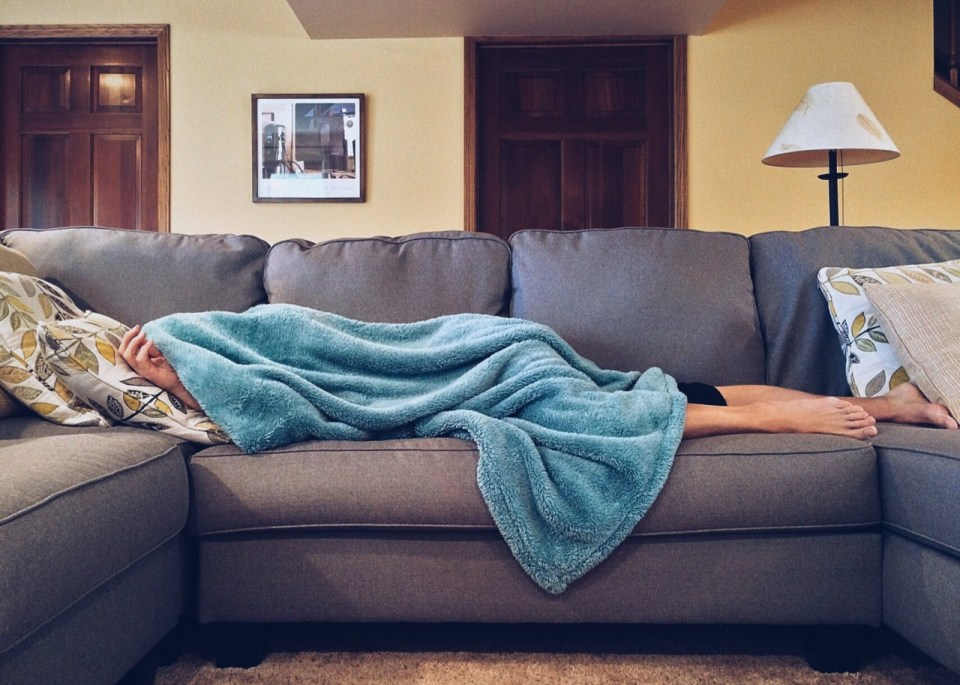 someone laying on a sofa with a blanket covering their body and head