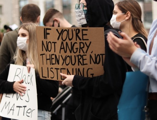 "People at a Black Lives Matter protest, wearing face masks due to Covid-19, and holding signs which say ""if you're not angry then you're not listening"" and ""black lives matter"""
