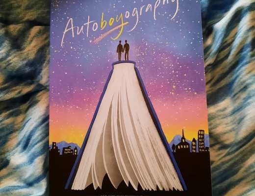 The book Autoboyography by Christina Lauren. The cover shows two silhouettes holding hands and standing on a giant book overlooking a city skyline at night.
