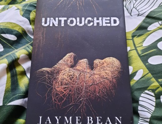 """A hardback copy of the book Untouched by Jayme Bean, which is a dark brown cover with a face on it covered in vines and the words """"some places are better left untouched"""" in white font"""