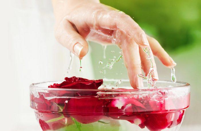 Maos dentro de um recipiente com água e pétalas de rosas