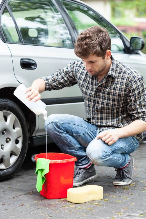 homem colocando sabao de carro num balde