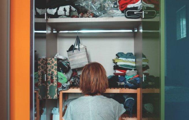 mulher olhando armário cheio e desarrumado