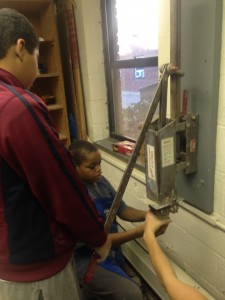 Isaiah and Jaden are using an extruder to form the clay.