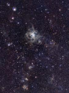 La Nebulosa de la Tarantula, a 170.000 años luz tiene una magnitud aparente de 8 (la absoluta es de -11). Si estuviese a la misma distancia de nosotros que la Nebulosa de Orión (que está a sólo 1.200), su magnitud aparente sería tal que podría proyectar sombras sobre nuestro planeta. Crédito: ESO/M.-R. Cioni/VISTA Magellanic Cloud survey