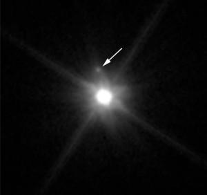 Esta imagen del telescopio Hubble muestra el primer satélite descubierto alrededor de Makemake. Crédito: NASA, ESA, y A. Parker y M. Buie (SwRI)