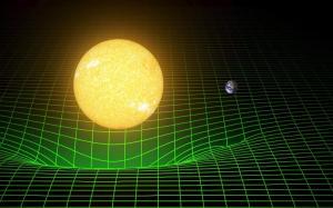Cuanto más masivo es un objeto, más distorsiona el espacio-tiempo, que aquí se muestra como una rejilla verde. La Tierra orbita alrededor del Sol moviéndose en esa depresión creada por la masa del Sol en la fábrica del espacio tiempo. No cae hacia la estrella porque también tiene su propio movimiento hacia delante. Crédito: LIGO/T. Pyle