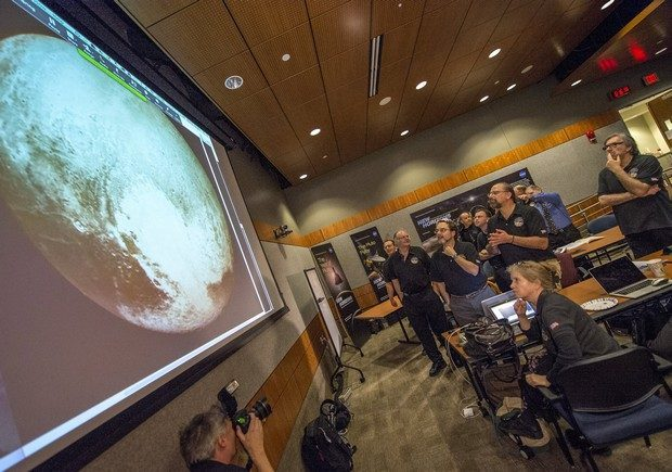 """Members of the New Horizons science team react to seeing the spacecraft's last and sharpest image of Pluto before closest approach later in the day at the Johns Hopkins University Applied Physics Laboratory (APL) in Laurel, Maryland July 14, 2015.More than nine years after its launch, a U.S. spacecraft sailed past Pluto on Tuesday, capping a 3 billion mile (4.88 billion km) journey to the solar system's farthest reaches, NASA said. The craft flew by the distant """"dwarf"""" planet at 7:49 a.m. after reaching a region beyond Neptune called the Kuiper Belt that was discovered in 1992. The achievement is the culmination of a 50-year effort to explore the solar system.    REUTERS/Bill Ingalls/NASA/Handout  ATTENTION EDITORS - FOR EDITORIAL USE ONLY. NOT FOR SALE FOR MARKETING OR ADVERTISING CAMPAIGNS. THIS IMAGE HAS BEEN SUPPLIED BY A THIRD PARTY. IT IS DISTRIBUTED, EXACTLY AS RECEIVED BY REUTERS, AS A SERVICE TO CLIENTS. MANDATORY CREDIT"""