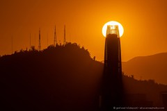 Solar eclipse, the sun is setting behind the Costanera Center in Santiago de Chile, the highest building in South America