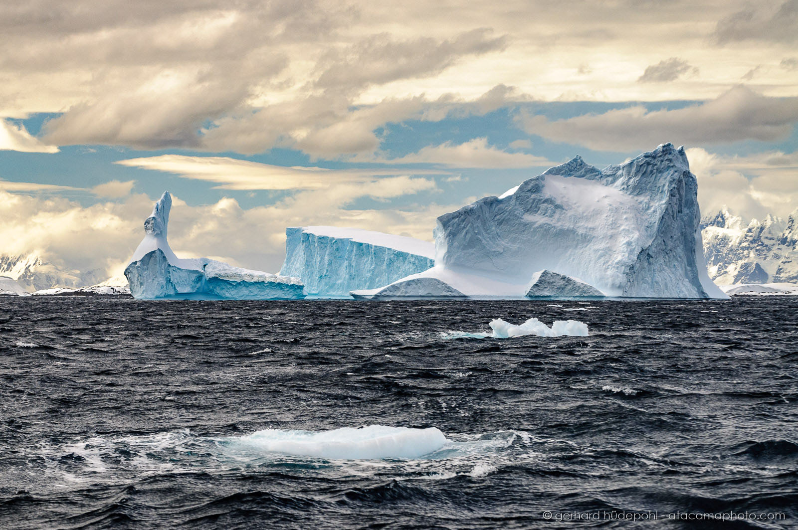 Frozen world of icebergs, mountains and clouds in Antarctica