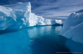 Deep blue is the only visible color when navigating between floating icebergs in Antarctica