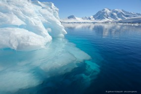 Iceberg with a view deep into the blue crystal clear waters of Antarctica