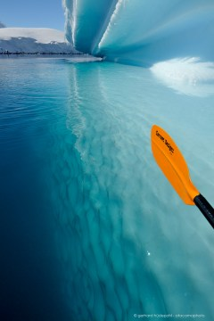 Crystal clear water allows a view to the bottom of an iceberg from a kayak in Antarctica