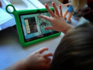 child using tablet computer to study biology- zooming in on screen on mid section of human skeleton