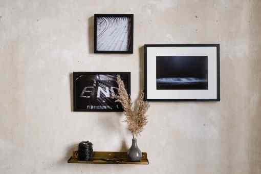 Wand mit drei Bildern in schwarzen Rahmen, Messingregal mit schwarzem Packband und Vase mit Trockenblumen