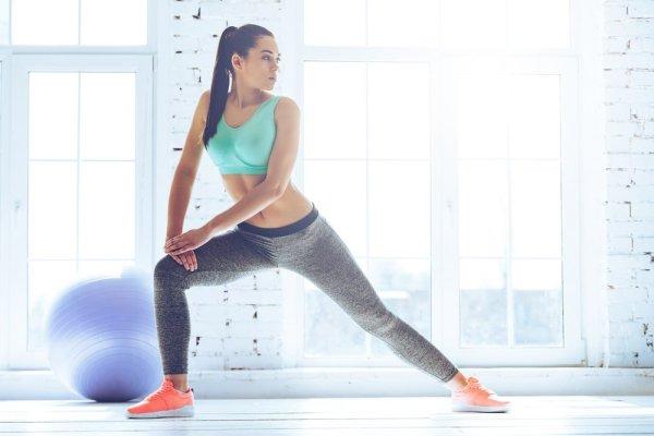 Photo d'une jeune femme avec brassière turquoise. Elle fait un personal training et entrainement fonctionnel. Dans le fond, il y a un swiss ball de couleur mauve