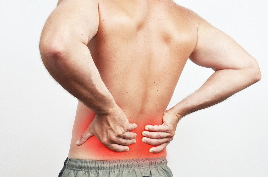 Photo montrant un homme se tenant le bas du dos. Il souffre des lombaires. Mal au dos