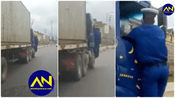 Police officer hanging on a speeding truck
