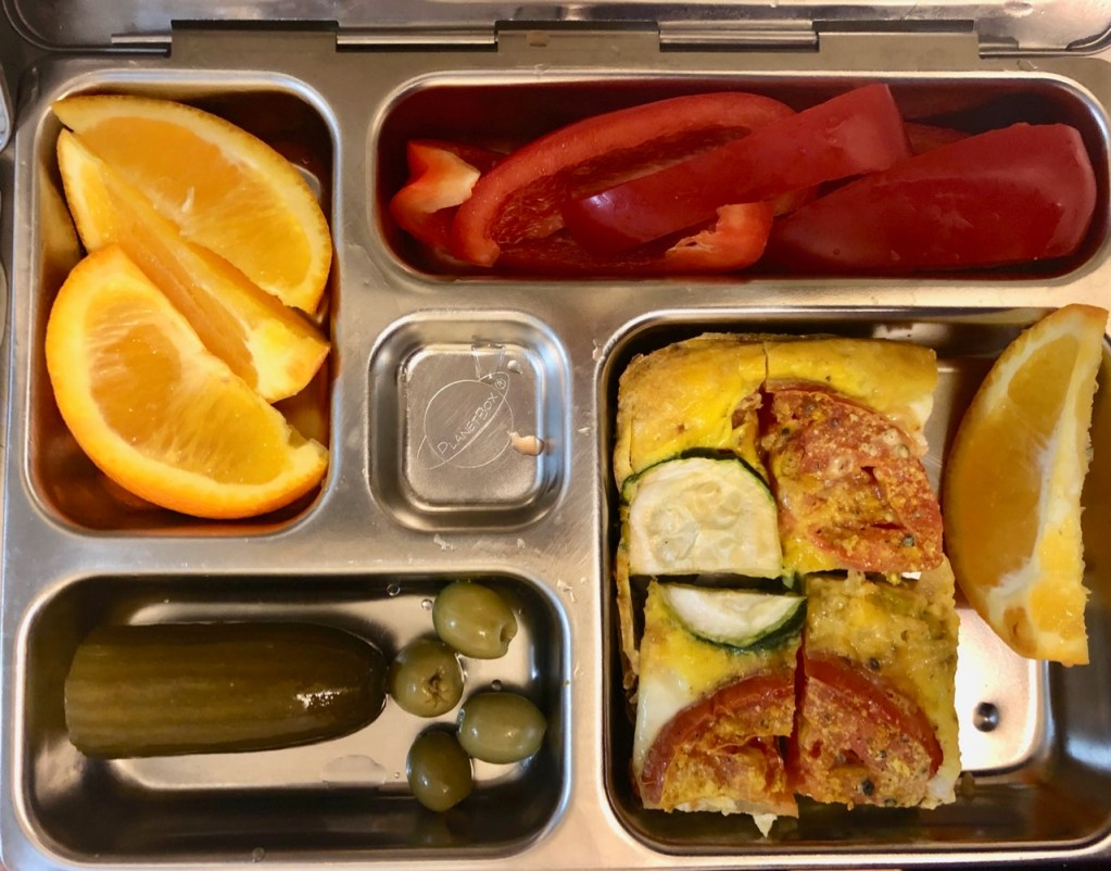 Vegetable quiche/ orange slices / red bell peppers / homemade pickle / olives