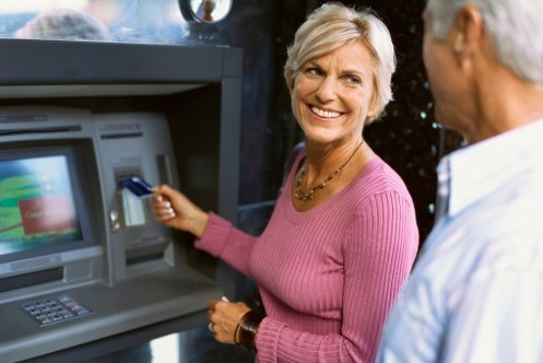 Happy Older Couple Using ATM