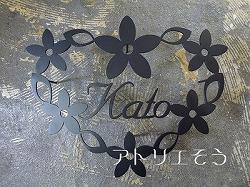 ロートアイアン風錆に強いステンレス製表札です。お花に囲まれた素敵な表札です。