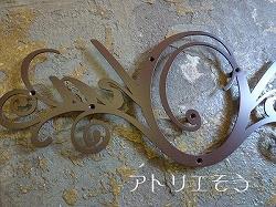 ロートアイアン風ステンレス製の妻飾り。Okaの文字をデザインした妻飾りです。