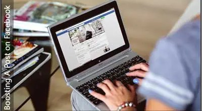 IImage of a woman typing on a laptop displaying facebook