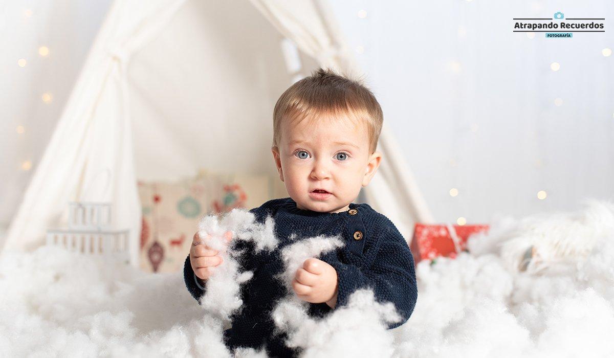 Foto infantil niño jugando con nieve en una sesión de fotos