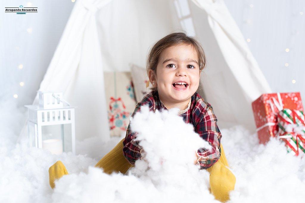 Fotografia de navidad infantil jugando con la nieve