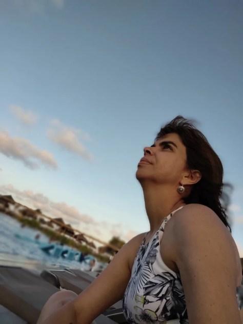 #PraCegoVer fotografia com mulher de perfil olhando para cima em primeiro plano na parte inferior da imagem, com fundo de piscina e céu azul desfocado