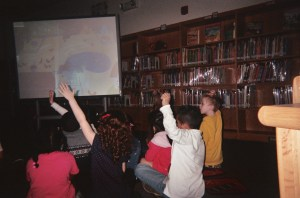 Children interact with their teacher, answering her question about a projected image they're responding to with enthusiasm.
