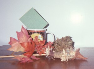Tuck the little scarecrow into a fall or Halloween arrangement using dollar store supplies.