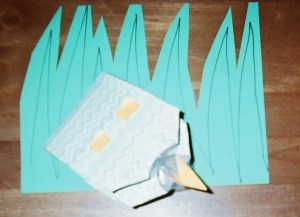 Re-used Tissue Box Puppet lives in a soft paper carpet of green grass.