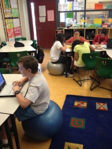 Seated on a large exercise ball, a fidgety fifth grader is able to stay focused.
