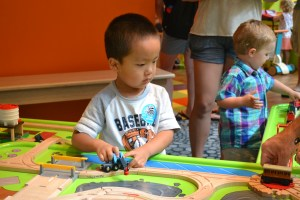 Young visitors to Marbles Kids' Museum play with trains around town.