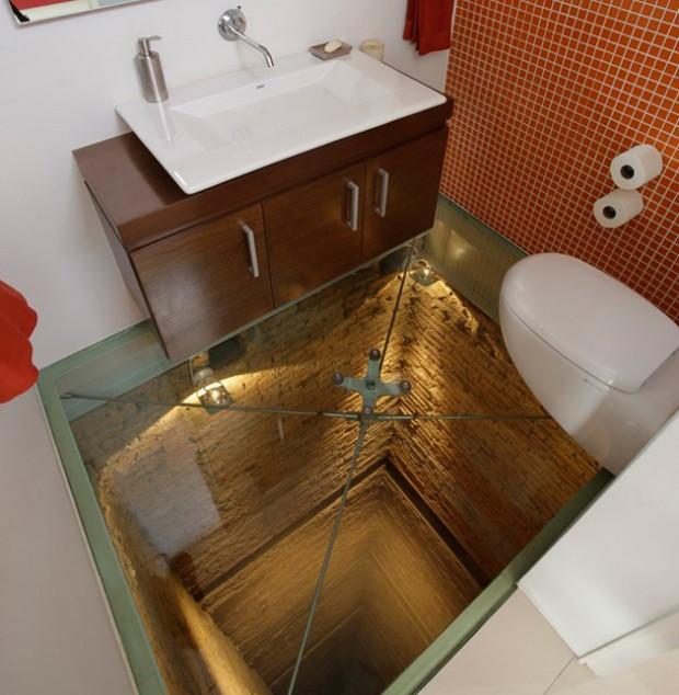 La toilette con pavimento in vetro e con vista nel vuoto.