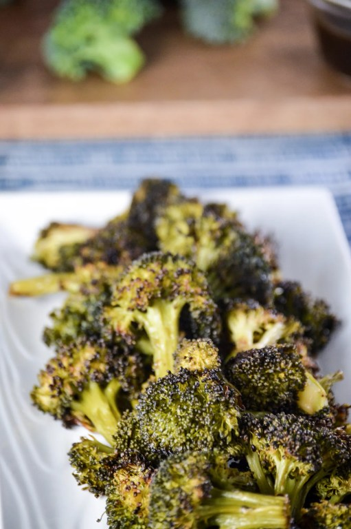 Picture is blackened broccoli on a angled white rectangle dish with cut up broccoli  in the background.  www.atwistedplate.com