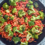 Top view of cast iron pan with chicken, broccoli, carrots, and red peppers. Cast iron is sitting on a teal and white towel. www.atwistedplate.com