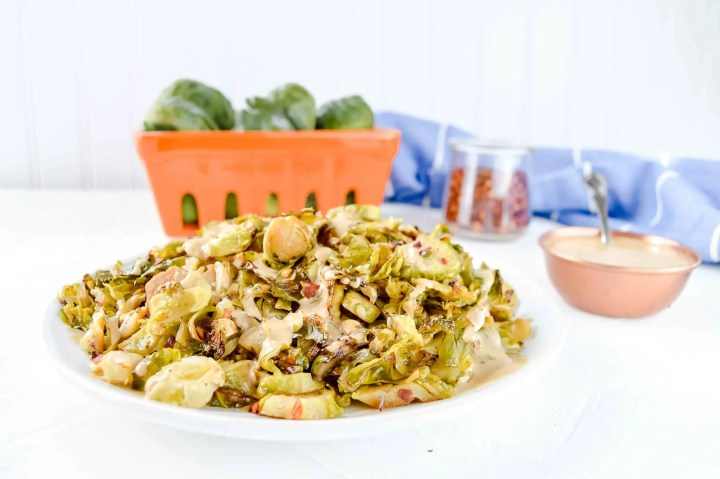 Crispy Brussel Sprouts with a Dijon Aioli on a white round plate. To the top right of the plate is a bowl of Dijon Aioli. There are Brussel sprouts around the plate. There is a blue and white towel at the top of the image. https://www.atwistedplate.com/crispy-brussel-sprouts-with-a-dijon-aioli/