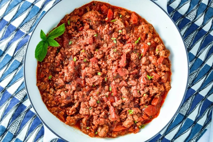 Overhead shot of Spicy Sausage Marinara in white dish with blue, white and black towel behind it. www.atwistedplate.com/spicy-sausage-marinara/