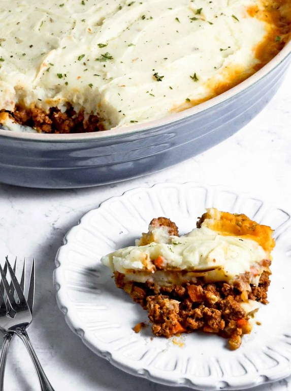 Shepherd Pie. Side angle of Shephards Pie in a blue dish with a serving of Shepherd's Pie on a white plate. www.atwistedplate.com