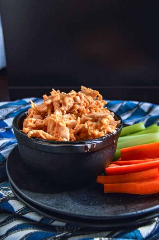 Side, slight angle view of Buffalo Chicken Dip in a black bowl on a black plate with celery and carrots.  Plate is sitting on a blue and white triangle towel against a dark background.  www.atwistedplate.com/buffalo-chicken-dip/