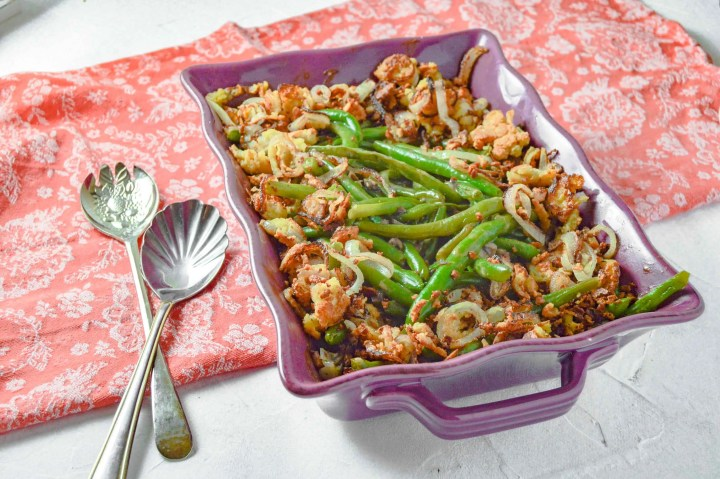ANGLED VIEW Dairy Free Green Bean Casserole in a purple dish on a pink towel. https://www.atwistedplate.com/green-bean-casserole-gluten-dairy-free/