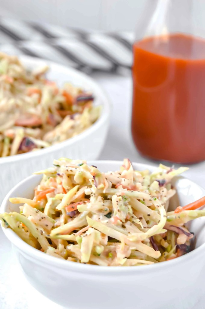 Buffalo Broccoli Slaw in a large white serving bowl and a small bow and a jar of hot sauce.  There is a black towel in the background.  www.atwistedplate.com