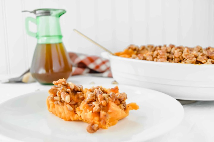 Side view images of Maple Walnut Sweet Potato Casserole plate of maple walnut sweet potato bake and a oval backing dish with a fall colored plaid towel, maple syrup in a green jar and walnuts scattered around. Above in purple script it says Maple & Walnut Sweet Potato Bake. www.atwistedplate.com/paleo-maple-walnut-sweet-potato-casserole/