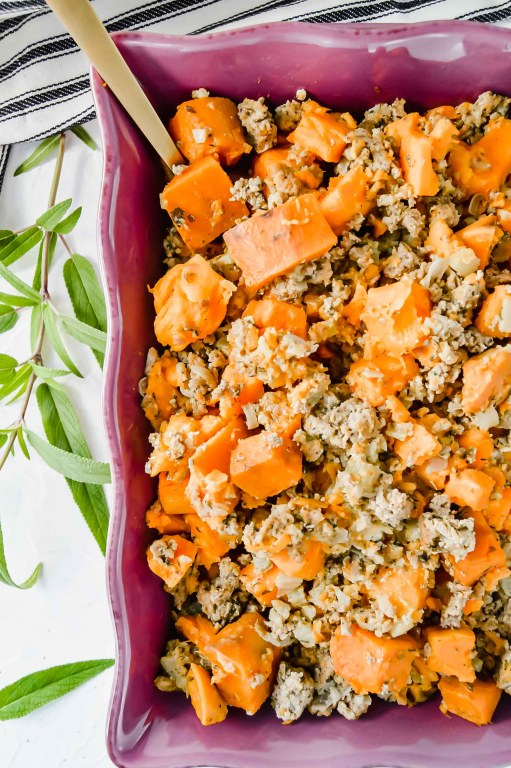 Image: Cut off top view of Sweet Potato Stuffing in a purple dish.  Around the dish are fresh sage leaves.  A black and white towel is at the top of the image.  https://www.atwistedplate.com/sweet-potato-stuffing-~-grain-free/