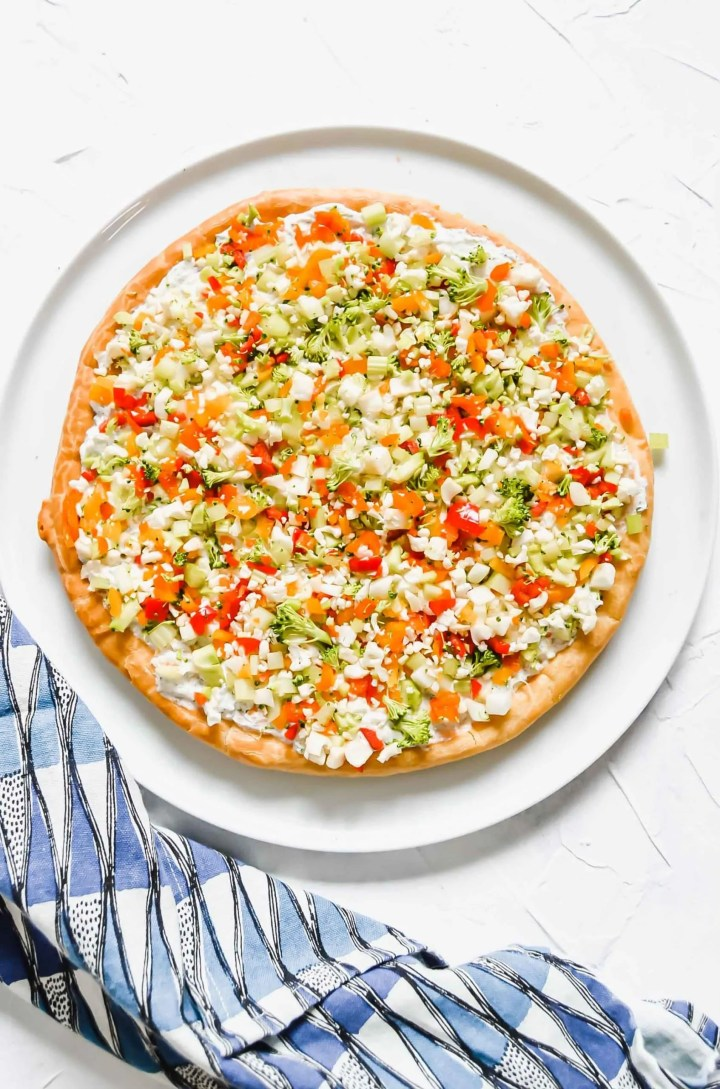 Top view of vegetable pizza against a white background with red, yellow and orange peppers, and a silver pizza cutter. www.atwistedplate.com/veggie-pizza/